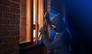 Einbrecher öffnet Fenster mit Brecheisen