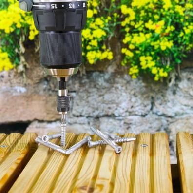 Bimetall-Terrassenschrauben Edelstahl A4 auf hellen Terrassendielen eine Schraube mit Akkuschrauber halb eingedreht